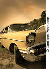 classic car - Head lamp of yellow classic car in sepia color...
