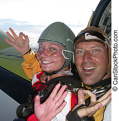 About to jump from aeroplane - two skdivers waving as they...