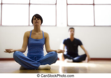 health club: man and women doing yoga. Dreamy atmosphere and...