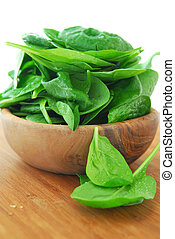 Spinach - Fresh spinach iin a wooden bowl on a cutting board
