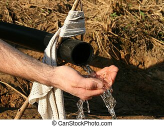 Water Pipe - A hand underneath a water pipe