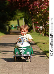 boy driving pedal car