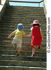 girl helping small boy up stairs