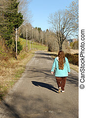 Walking a Forest Road - A woman in turquise coat walks along...