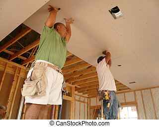 Holding up the Sheet - Two workers putting Sheetrock on the...
