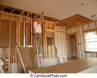 Drilling the Sheetrock - Worker standing on stilts while he...