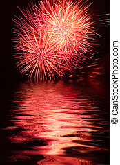 Fireworks Over Water - Exploding colorful fireworks against...