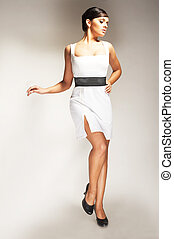 Fashion model Posed on light background in white dress