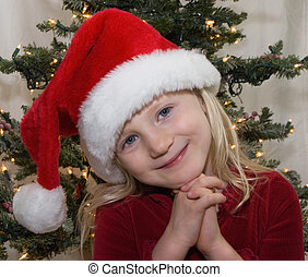 Christmas Girl - Young girl wearing a santa hat with...