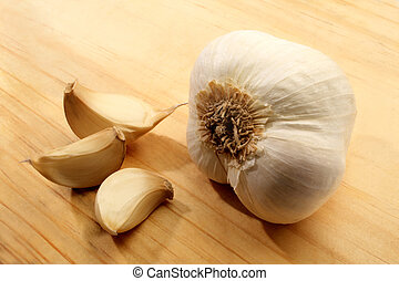 Garlic cloves displayed on a wooden cutting board.