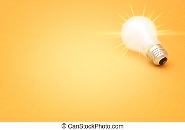 Background with lit lightbulb. Isolated on yellow