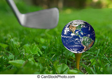 Earth on golf tee from the ground level with grass and...