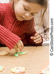 Decorating - Little girl decorating cookies for christmas...