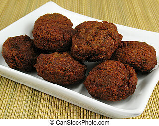 Falafels - A mound of fresh, hot falafels on a white plate....