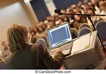 Lecture at Convention - Business woman at podium with laptop...