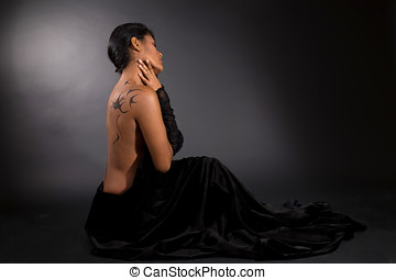 Mysterious beauty - Beautiful woman sitting on black...