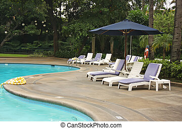Poolside deck chairs tropical setting blue umbrellas