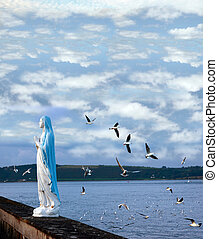 on a wing and a prayer - statue of the virgin mary with...