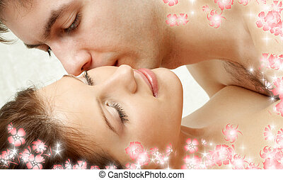 foreplay with flowers - sweet couple kissing in bed with...