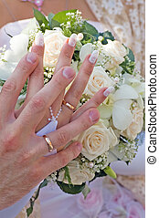 wedding hands - two hands with rings on wedding bouquet