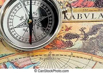 Compass and map - Silver metal compass on the old map