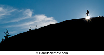 Silhouetted hiker - A hiker pauses along a ridge