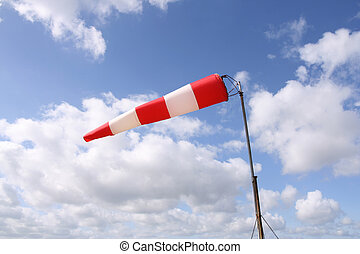 Windsock horizontal - Red and white windsock blows against a...