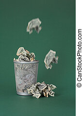 Wasted money - Dollar bills - Photo of a waste basket full...