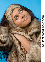 woman in fur coat - young woman in fur coat isolated on blue