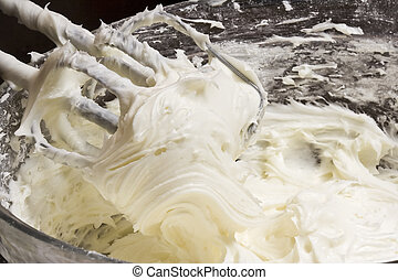 frosty - close up of cream cheese frosting mixed up in a...