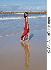 Lady in red - Beautiful girl in red dress on the beach