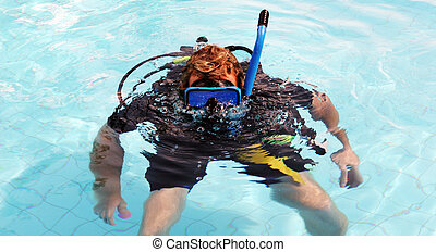 Happy scuba diver in the swimming pool blowing bubbles.