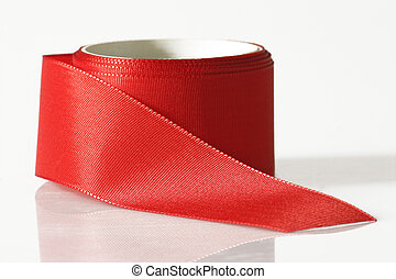 Red ribbon rolled on bright background