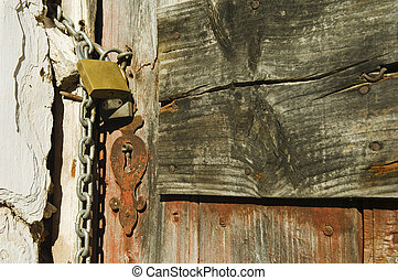 Old door - Old drab door secured with a padlock and iron...