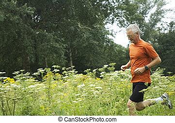 Running Senior Man - Senior man is running through a field...
