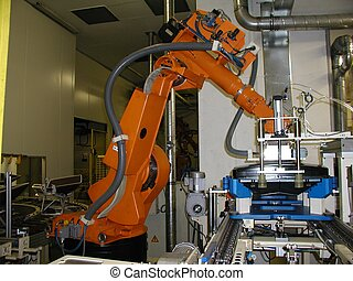 Orange robot standby for next work process - This robot...