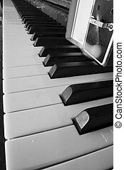 piano keyboard and metronome - detail of a piano keyboard...