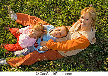 Kids and woman laying in the grass in the autumn afternoon