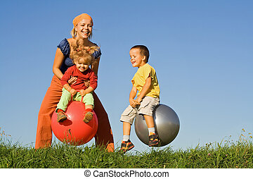 Jumping in the grass - Kids with their mother jumping in the...
