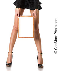 Frame in hands - woman in sexy blacki skirt holding wooden...