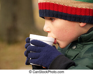 winter boy drinking cocoa - young boy with hat and gloves...