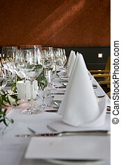 Well-laid table with white folded serviettes and wine...