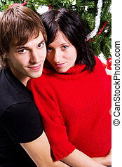 young couple expecting a baby christmas tree in background
