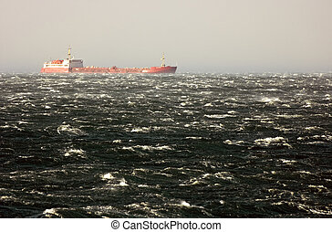 Storm on the sea - Merchant ship ploughing the waves of a...