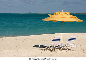 yellow shade - sun loungers under umbrellas on tropical...