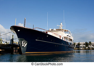 blue super yacht - blue hull luxury motor yacht tied to dock