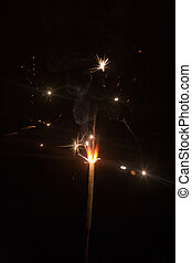 New Years stars - Bengal fire sparking in the dark, close-up...