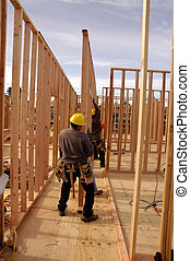 Hispanic carpenters setting a wall at a House under...