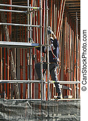 Worker and scaffold - A construction worker with safety...