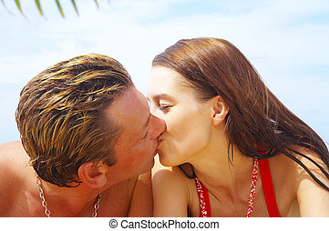 summer kiss - a portrait of attractive couple having kiss on...